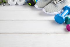 Sport and fitness symbols - sneakers, water and dumbbell on wood. En wall background stock photography