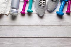 Sport and fitness symbols - sneakers, water, towel and dumbbell. On white wooden wall background stock photography