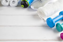 Sport and fitness symbols - sneakers, water, towel and dumbbell. On white wooden wall background stock image