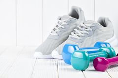 Sport and fitness symbols - sports shoes and colorful dumbbell. On wooden wall background royalty free stock image