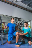 Sport, fitness, teamwork, bodybuilding people concept - man and personal trainer with barbell flexing muscles in gym