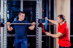 Sport, fitness, teamwork, bodybuilding people concept - man and personal trainer with barbell flexing muscles in gym Stock Photo