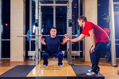 Sport, fitness, teamwork, bodybuilding people concept - man and personal trainer with barbell flexing muscles in gym Stock Images