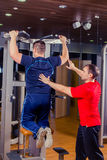 Sport, fitness, teamwork, bodybuilding people concept - man and personal trainer with barbell weight lifting group Stock Image