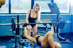 Sport, fitness, teamwork, bodybuilding and people concept - young woman and personal trainer with barbell flexing stock photo