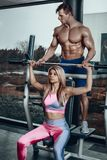 Sport, fitness, teamwork, bodybuilding and people concept - young woman and personal trainer with barbell flexing stock photography