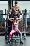 Sport, fitness, teamwork, bodybuilding and people concept - young woman and personal trainer with barbell flexing stock image
