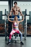 Sport, fitness, teamwork, bodybuilding and people concept - young woman and personal trainer with barbell flexing royalty free stock images