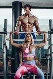 Sport, fitness, teamwork, bodybuilding and people concept - young woman and personal trainer with barbell flexing royalty free stock photos