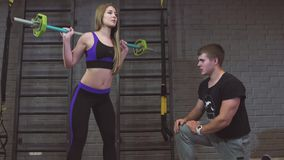 Sport, fitness, teamwork, bodybuilding and people. Young woman and personal trainer with barbell flexing muscles in gym. 4k stock video