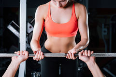 Sport, fitness, teamwork, weightlifting and people concept - young girl personal trainer work with man  barbell Royalty Free Stock Images