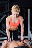 Sport, fitness, teamwork, weightlifting and people concept - young girl personal trainer work with man  barbell. Sport, fitness, teamwork, weightlifting and Stock Image