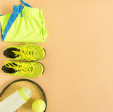 Sport, fitness, tennis, healthy lifestyle, sport stuff. Tennis racket, lime trainers, tennis ball, lime athletic shorts, sports bo Stock Photos