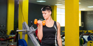 Sport, fitness, training and lifestyle concept - Fitness girl with dumbbells on a gym royalty free stock images