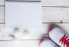 Sport fitness, weight loss concept. Ping pong racket, balls, notepad, sneakers on white wooden background. Vintage retro instagram filter royalty free stock photo