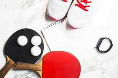 Sport fitness, weight loss concept. Ping pong racket, balls, notepad, sneakers on white wooden background. Vintage retro instagram filter stock image