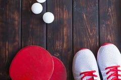 Sport fitness, weight loss concept. Ping pong racket, balls, sneakers on dark wooden background. Vintage retro instagram filter royalty free stock photos