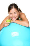 Sport fitness woman. On exercise pilates ball eating an apple relaxing taking a break. Smiling happy multiracial female fitness model isolated on white Stock Images