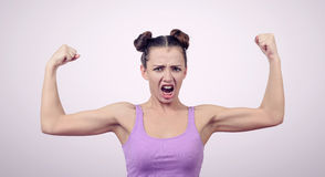 Sport fitness woman flexing show her biceps muscles on background Royalty Free Stock Images