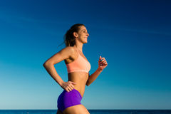 Sport and Fitness - woman jogging. Under clear blue sky Royalty Free Stock Photography
