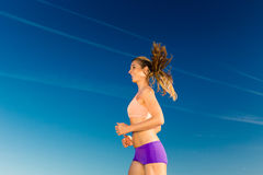 Sport and Fitness - woman jogging. Under clear blue sky Royalty Free Stock Photo