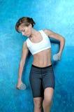 Sport fitness woman near a blue wall Stock Image