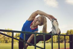 Sport fitness woman stretching on the stadium. Sport blonde girl stretching arms in sport running arena with many tracks Royalty Free Stock Photos