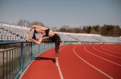 Sport fitness woman stretching on the stadium.Sport blond girl stretching arms in sport running arena with many tracks. royalty free stock images