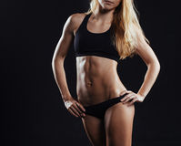 Sport fitness woman with strong muscles on black background Stock Images