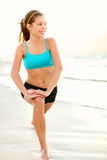 Sport fitness woman training on beach. Stretching out legs after running or jogging outside. Beautiful young fit multicultural mixed race Caucasian / Asian Royalty Free Stock Photo