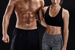Sport, fitness, workout concept. Fit couple, strong muscular man and slim woman posing on a black background. Sport, fitness, workout concept. Fit couple, strong stock photography