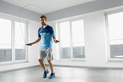Sport Fitness Workout. Healthy Man Skipping Jump Rope Indoors. Sport And Fitness Workout. Healthy Athletic Man With Muscular Body In Fashion Headphones royalty free stock photography