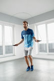 Sport Fitness Workout. Healthy Man Skipping Jump Rope Indoors. Royalty Free Stock Photo