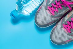 Sport flat lay pink shoes and bottle of water on blue background with copyspace for your text. Concept healthy lifestyle and diet royalty free stock image