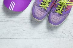 Sport flat lay purple shoes and cap on white wooden background with copyspace for your text. Concept healthy lifestyle and diet.  stock photos