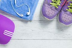 Sport flat lay purple shoes and cap on white wooden background with copyspace for your text. Concept healthy lifestyle and diet. Sport flat lay purple shoes and royalty free stock photography