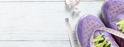 Sport flat lay purple shoes and measuring tape on white wooden background. Banner size with copy space for your text. royalty free stock photos