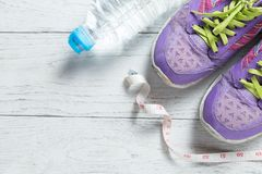 Sport flat lay purple shoes and measuring tape on white wooden background with copyspace for your text. Concept healthy lifestyle royalty free stock image