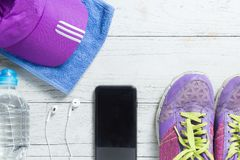 Sport flat lay purple shoes, smartphone and workout equipments on white wooden background with copyspace for your text. stock image