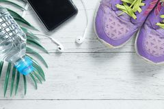 Sport flat lay purple shoes, smartphone and workout equipments on white wooden background with copyspace for your text. royalty free stock photography