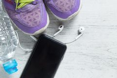 Sport flat lay purple shoes, smartphone and workout equipments on white wooden background with copyspace for your text. stock images