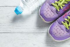 Sport flat lay purple shoes and water bottle on white wooden background with copyspace for your text. Concept healthy lifestyle royalty free stock photos