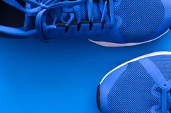 Sport flatlay background. Blue sport sneakers for running on the blue background with copy space royalty free stock photography