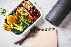 Sport food concept. Lunch box with heathy food, notebook and mat on a gray background