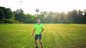 Sport, football and people - soccer player playing and juggling with ball on field stock footage