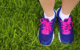 Sport Footwear on Female Feet on Green Grass. Closeup Stock Photography