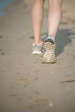 Sport footwear, sand footprints and legs close up. Runner feet d Stock Photography