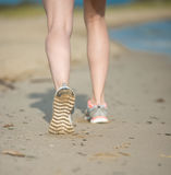 Sport footwear, sand footprints and legs close up. Runner feet d Stock Photos