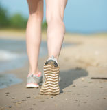 Sport footwear, sand footprints and legs close up. Runner feet d Royalty Free Stock Photo