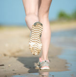Sport footwear, sand footprints and legs close up Stock Photo